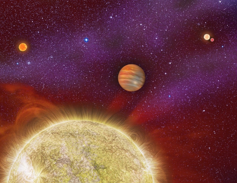 """Planet With Four Stars: This artist's conception shows the 30 Ari system, which includes four stars and a planet. The planet, a gas giant, orbits its primary star (yellow) in about a year's time. The primary star, called 30 Ari B, has a companion -- the small """"red dwarf"""" star shown at upper left. This pair of stars is itself locked in a long-distance orbit with another pair of stars (upper right), known as 30 Ari A. Researchers using instruments at the Palomar Observatory near San Diego, Calif., recently discovered the red star at upper left, bringing the total number of known stars in the system from three to four.  Image: Karen Teramura, UH IfA"""
