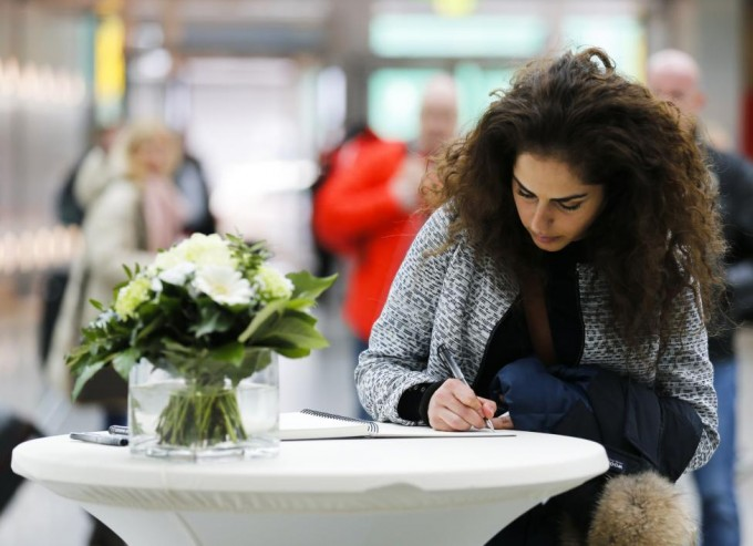 A woman writes in a book of condolences in Duesseldorf airport
