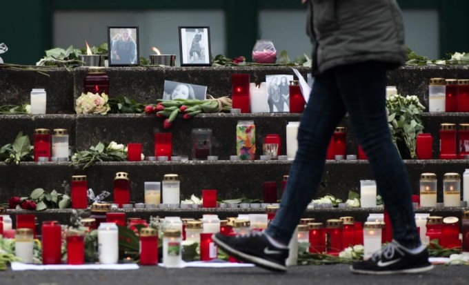 A girl walks past candles and photos in front of the Joseph-Koenig-Gymnasium high school in Haltern am See, Germany March, 25, 2015. Students and teachers at a small-town German high school broke out in ears when they realised that 16 classmates and two teachers were on board an ill-fated Germanwings airplane that crashed in France on a flight home to Duesseldorf. REUTERS/Ina Fassbender