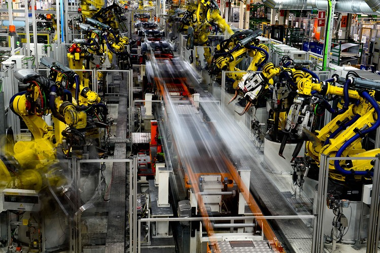 Robots work on vehicles on the production line during assembly at Volkswagen AG's Seat automobile plant in Martorell, Spain, earlier this year. [Reuters]