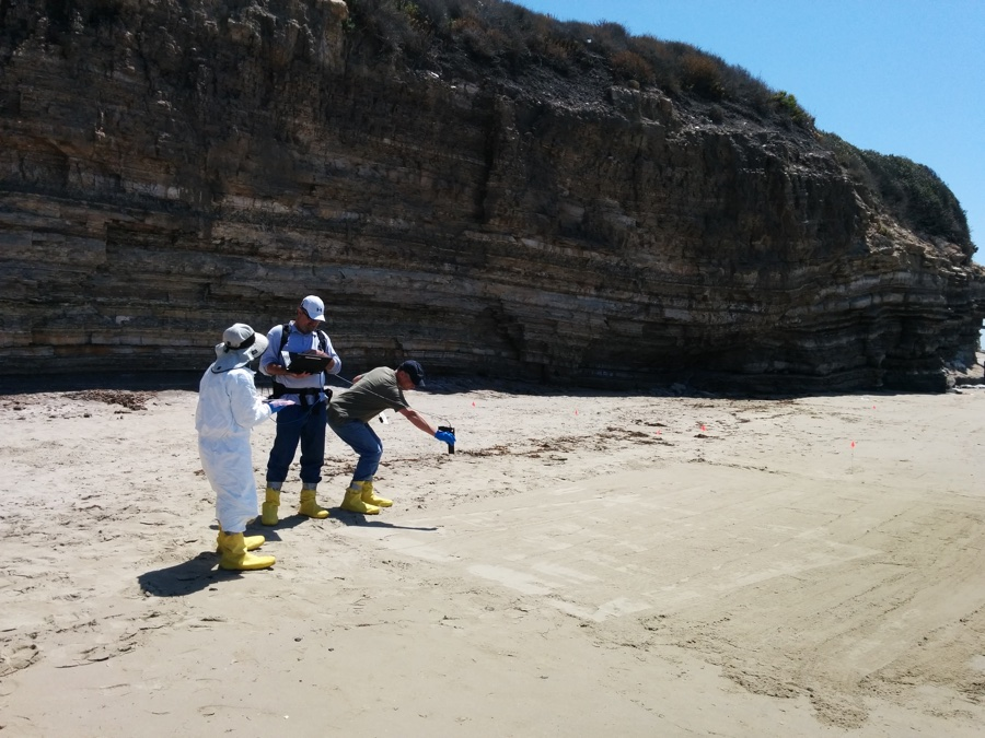Members of the AVIRIS-NG team, including citizen scientists, take spectral measurements of tar on a beach affected by the oil spill. The measurements were used to validate the AVIRIS-NG aerial data. Photo by Mike Glick, citizen scientist.