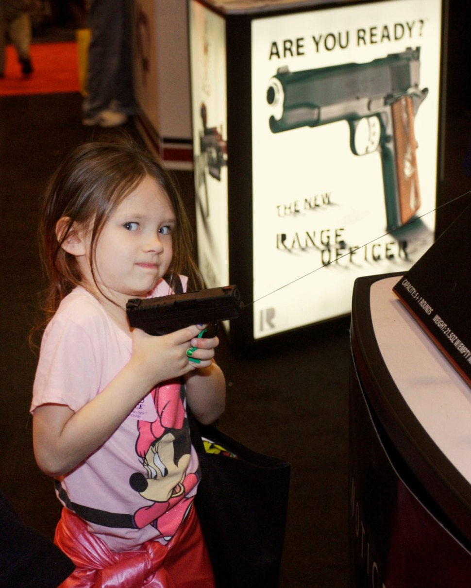 A young girl with a working handgun at an NRA convention. [REUTERS]