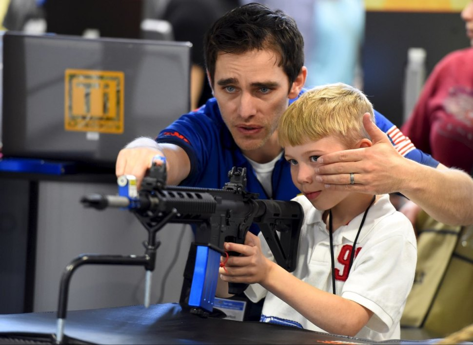 A man shows a boy how to sight down an electronic rifle at an NRA meeting. [Reuters]