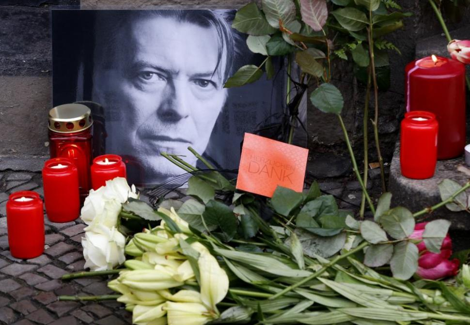 Flowers and lit candles are pictured next to a portrait of David Bowie outside the apartment house where he was living in 1976-78 in Berlin's Schoeneberg district