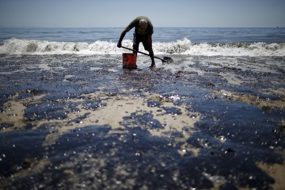 William McConnaughey, 56, who drove from San Diego to help shovel oil off the beach, stands in an oil slick in bare feet along the coast of Refugio State Beach in Goleta, California, United States, May 20, 2015.  REUTERS/Lucy Nicholson