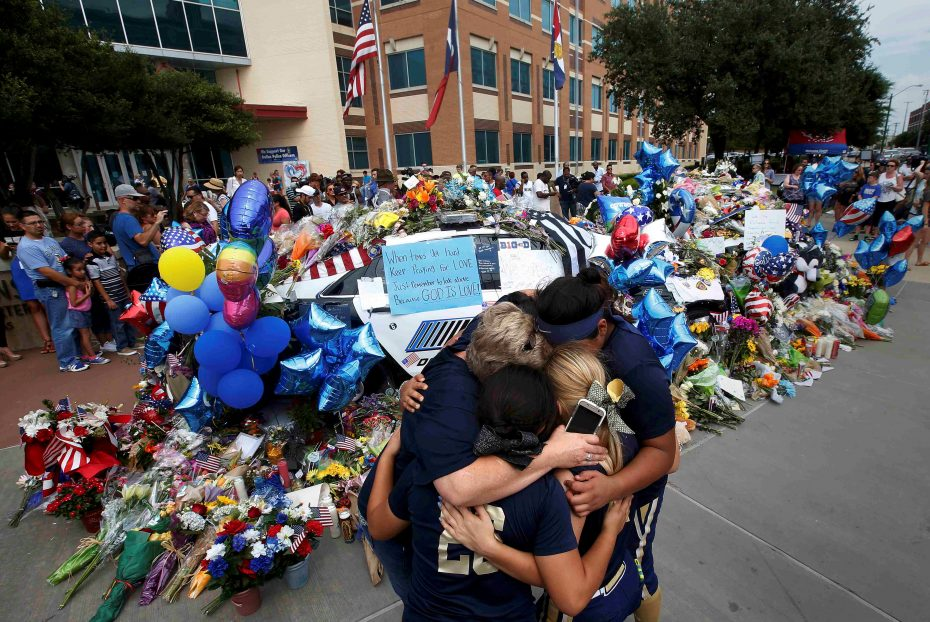 A softball team hugs after paying their respects at a makeshift memorial at Dallas Police Headquarters following the multiple police shootings in Dallas, Texas, U.S., July 9, 2016.   REUTERS/Carlo Allegri