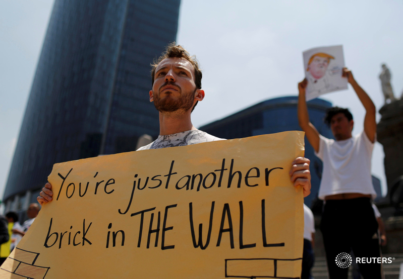 Demonstrators hold placards during a protest against Trump's visit, at the Angel of Independence monument in Mexico City. REUTERS/Tomas Bravo