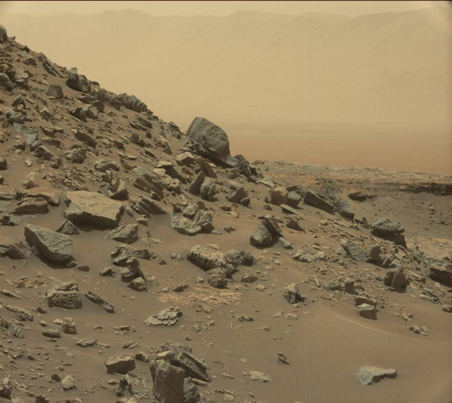 The rim of Gale Crater is visible in the distance, through the dusty haze, in this Curiosity view of a sloping hillside on Mount Sharp. Image Credit: NASA/JPL-Caltech/MSSS