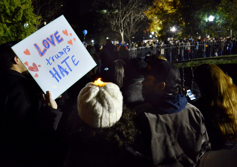 "A demonstrator holds a ""Love Trumps Hate"" placard during a candlelight vigil against President-elect Donald Trump's election, in Lafayette Park, near the White House, in Washington, U.S., November 12, 2016.           REUTERS/Mike Theiler"