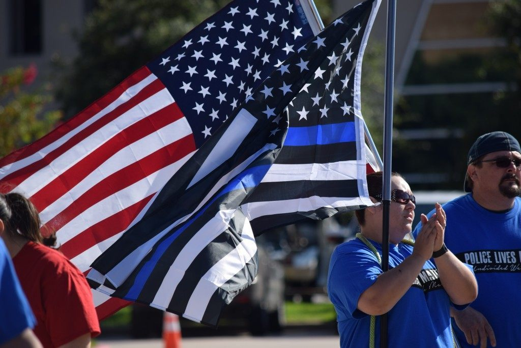 """Carrying the American and """"Thin Blue Line"""" flags during the #PoliceLivesMatter march in Houston. (Photo: Breitbart Texas/Bob Price)"""