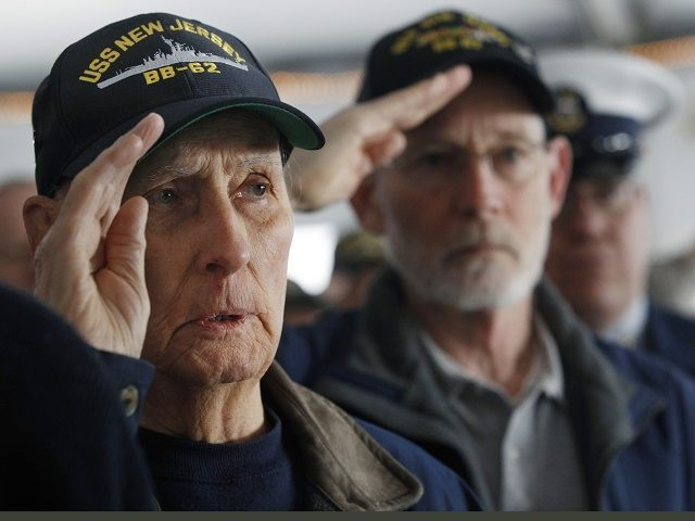 World War II veteran and original crew member of the battleship New Jersey, Russell Collins, left, salutes with others on the battleship during a commemoration of the 74th anniversary of the attack on Pearl Harbor, Monday, Dec. 7, 2015, in Camden, N.J. In Pearl Harbor, the U.S. Navy and National Park Service hosted a ceremony in remembrance of those killed on Dec. 7, 1941. (AP Photo/Mel Evans)
