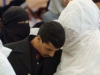 AMMAN, JORDAN - JULY 25: A Groom listens to his veiled bride in a mass wedding July 25, 2003 in Amman, Jordan. One hundred and four brides and grooms made the knot in a mass wedding organized by the Islamic society of (al-Afaf) for philanthropic wedding, celebrating with their families and friends in a non-mixed party between males and females. (Photo by Salah Malkawi/Getty Images)