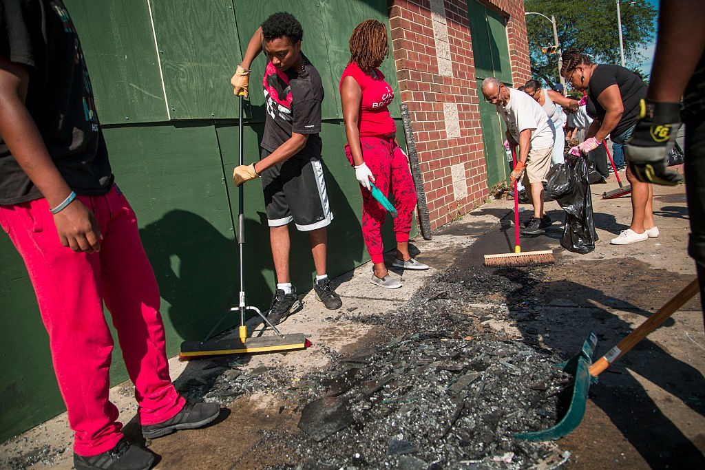 MILWAUKEE, WI - AUGUST 14: Community members and volunteers help clean up the damage to a few local business after rioters clashed with the Milwaukee Police Department protesting an officer involved killing August 14, 2016 in Milwaukee, Wisconsin. Hundreds of angry people confronted police after an officer shot and killed a fleeing armed man earlier in the day. (Photo by Darren Hauck/Getty Images)