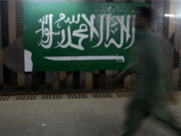 A man walks beside the Saudi flag at the popular market of Qabil street in the heart of Jeddah historic center on December 9, 2015 in Jeddah, Saudi Arabia. The street which is one of the oldest business streets that dates back to early days of 20th century, got its name from the Qabil family that owned land originally.