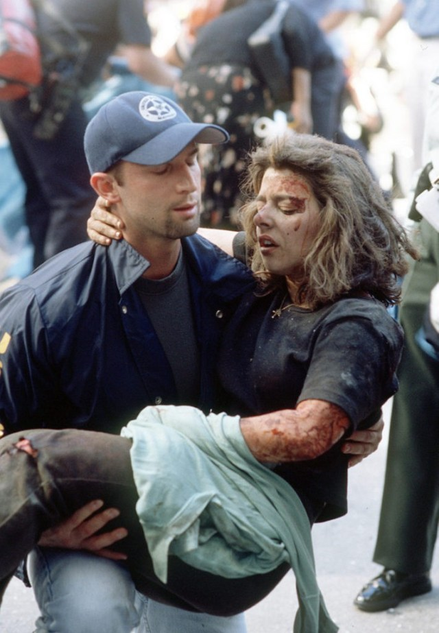 Deputy U.S. marshal Dominic Guadagnoli helps a women after she was injured in the terrorist attack on the World Trade Center in New York, Tuesday, Sept. 11, 2001. (AP Photo/Gulnara Samoilova)