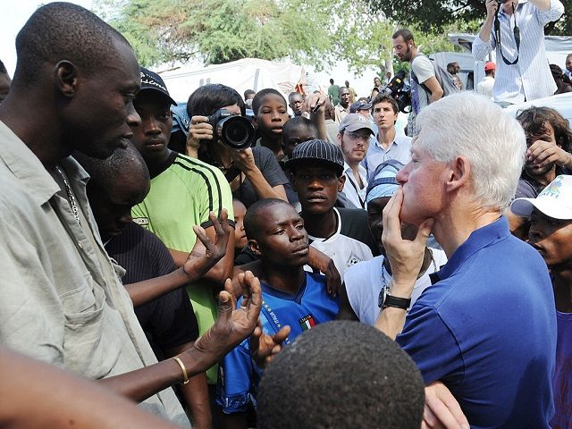 "Former US president and UN Special Envoy for Haiti Bill Clinton (R) listens to local residents on October 6, 2010 in a city camp in Port-au-Prince. The Clinton Foundation announced that it will, through its Haiti Relief Fund - provide 500,000 USD in bridge funding for a camp in Petionville run by the J/P Haitian Relief Organization. ""Rebuilding housing for more than 1 million people displaced by the earthquake will take time, as teams on the ground continue to clear rubble and build infrastructure, including water and sanitation systems,"" President Clinton said. AFP PHOTO/ Thony BELIZAIRE (Photo credit should read THONY BELIZAIRE/AFP/Getty Images)"