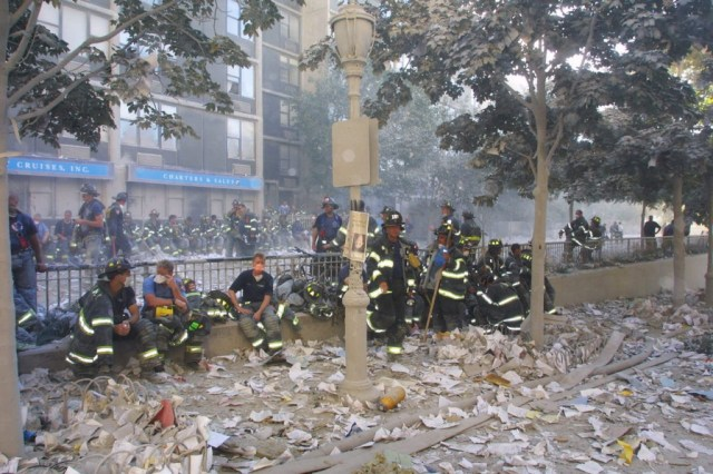 394277 10: New York City firefighters take a rest frm rescue operations at the World Trade Center after two hijacked planes crashed into the Twin Towers September 11, 2001 in New York. (Photo by Ron Agam/Getty Images)