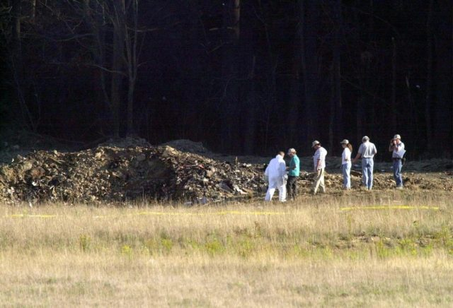 SHANKSVILLE, UNITED STATES: 7/10 US-ATTACKS-2ND YEAR ANNIVERSARY Officials examine the crater 11 Septemner 2001 at the crash site of United Airlines Flight 93 in Shanksville, Pennsylvania. The plane from Newark, New Jersey, and bound for San Francisco, California, was hijacked and crashed in the field killing al on board. The all-out war on terrorism unleashed by Washington after the attacks marked a turning point in US-Arab relations and nowhere more so than in once top ally Saudi Arabia. With 15 of the 19 suicide hijackers carrying Saudi nationality and mastermind Osama bin Laden being the scion of a leading Saudi family, the desert kingdom and world oil kingpin, suddenly found itself on the frontline of the war on terror prosecuted by US President George W. Bush. AFP PHOTO/David MAXWELL (Photo credit should read DAVID MAXWELL/AFP/Getty Images)
