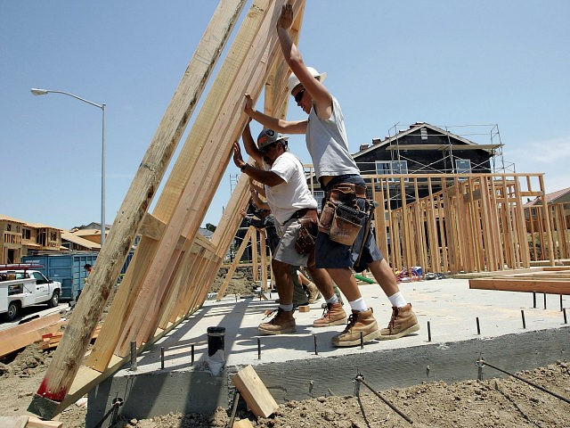 RICHMOND, CA - JUNE 26: Construction workers raise wood framing as they build homes in a new housing development June 26, 2006 in Richmond, California. A report issued by the U.S. Commerce Department stated that sales of new single-family homes were up 4.6 percent in May. The median price of homes sold in May slipped to $235,300, down 4.3 percent from April. (Photo by Justin Sullivan/Getty Images)