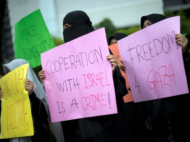 Anti-Israel protesters hold up placards as a group marches towards the US embassy during a protest in Kuala Lumpur on November 23, 2012. Dozens of students after offering their Friday prayers marched towards the US embassy while holding placards and banners to condemn Israel military aggression in Gaza and demanded the US be sincere in its efforts in the crisis. AFP PHOTO / Saeed KHAN (Photo credit should read SAEED KHAN/AFP/Getty Images)