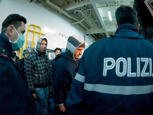 Italian Police escort would-be migrants believed to be from North Africa as they are disembarked off a ferry boat in the Sicilian port of Porto Empedocle, Italy, early Sunday, Feb. 13, 2011 after their boat reached the island of Lampedusa from North Africa. Italy has ferried hundreds of Tunisians off a tiny Sicilian island to detention centers amid government fears that terrorists could mix in among the boatloads of people fleeing turmoil in North Africa. By dawn Saturday, around 3,000 migrants had arrived by boat on Lampedusa over three days, hundreds more arrived during the day and several more boats were reportedly spotted on the horizon headed for the flat-rock, largely barren fishing island, Italian authorities said. (AP Photo/Daniele La Monaca)