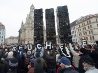 """TOPSHOT - Demonstrators hold up posters reading """"hypocrisy"""" as they protest against an installation made of buses titled """"Monument"""" by Syrian-born artist Manaf Halbouni erected at the Neumarkt square close to the Frauenkirche (Church of Our Lady) in Dresden, eastern Germany, on February 7, 2017. The artwork, that aims to evoke the barricades set up in the war-torn eastern city of Aleppo and the suffering of the people of Syria, has drawn fierce criticism from far-right groups. / AFP / dpa / Sebastian Kahnert / Germany OUT        (Photo credit should read SEBASTIAN KAHNERT/AFP/Getty Images)"""