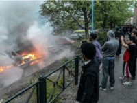 Bystanders take photos of a row of burning cars in the Stockholm suburb of Rinkeby after youths rioted in several different suburbs around Stockholm, Sweden for a fourth consecutive night on May 23, 2013. In the suburb of Husby, where the riots began on Sunday in response to the fatal police shooting of a 69-year-old machete-wielding man, 80 percent of residents are immigrants and the unrest has highlighted Sweden's failure to integrate swathes of its immigrant population, but in this small, consensus-driven country, there was little agreement on how to solve the problem.   AFP PHOTO /SCANPIX SWEDEN/ FREDRIK SANDBERG     SWEDEN OUT