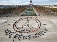 """Environmentalist activists form a human chain representing the peace sign and the spelling out """"100% renewable"""", on the side line of the COP21, United Nations Climate Change Conference near the Eiffel Tower in Paris, Sunday, Dec. 6, 2015. Negotiators adopted a draft climate agreement Saturday that was cluttered with brackets and competing options, leaving ministers with the job of untangling key sticking points in what is envisioned to become a lasting, universal pact to fight global warming. (AP Photo/Michel Euler)"""