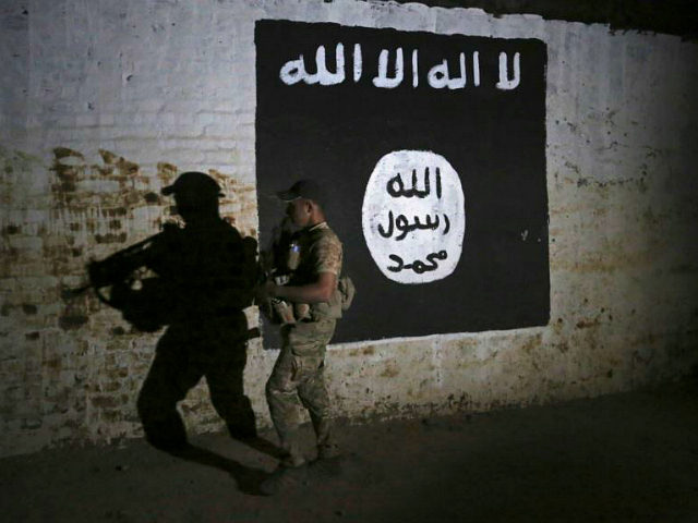 FILE - In this March 1, 2017 file photo, an Iraqi soldier inspects a recently-discovered train tunnel, adorned with an Islamic State group flag, that belonged to the former Baghdad to Mosul line, that was turned it to a training camp for IS fighters, in western Mosul, Iraq. Some 40 square kilometers on the western bank of the Tigris River is the Islamic State group's last major stand in Iraq. In addition to Mosul's so-called right bank, IS still controls a handful of small pockets of Iraqi territory and a swath of Syria's north including the group's self-proclaimed capital, Raqqa. (AP Photo/Khalid Mohammed, File)