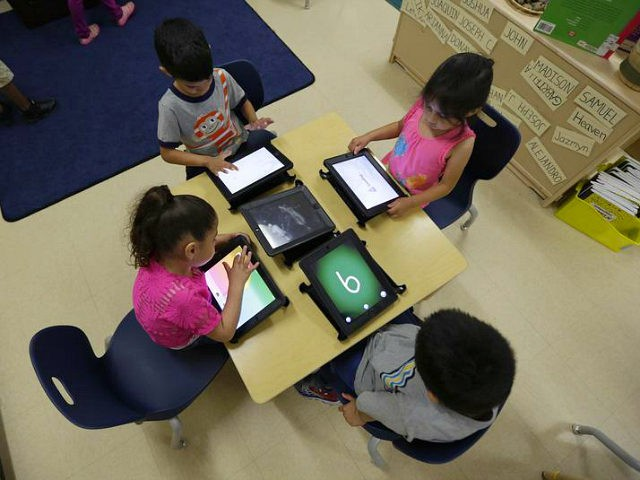FILE - In this April 2, 2014 file photo, Pre-K students use electronic tablets at the South Education Center in San Antonio. As Gov. Rick Perry wraps up a record 14 years on the job, Republican Greg Abbott and Democrat Wendy Davis are both vowing to make public schools a top-line agenda if elected in November. Following through could make public schools a signature issue for a Texas governor as it was under George W. Bush, before he left for the White House and used the state's testing system as the framework for No Child Left Behind. (AP Photo/Eric Gay, File)