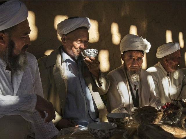 TURPAN, CHINA - SEPTEMBER 13: (CHINA OUT) Uyghur men gather for a holiday meal during the Corban Festival on September 13, 2016 in Turpan County, in the far western Xinjiang province, China. The Corban festival, known to Muslims worldwide as Eid al-Adha or 'feast of the sacrifice', is celebrated by ethnic Uyghurs across Xinjiang, the far-western region of China bordering Central Asia that is home to roughly half of the country's 23 million Muslims. The festival, considered the most important of the year, involves religious rites and visits to the graves of relatives, as well as sharing meals with family. Although Islam is a 'recognized' religion in the constitution of officially atheist China, ethnic Uyghurs are subjected to restrictions on religious and cultural practices that are imposed by China's Communist Party. Ethnic tensions have fueled violence that Chinese authorities point to as justification for the restrictions. (Photo by Kevin Frayer/Getty Images)