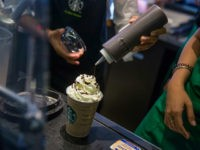 An employee pours syrup over whipped cream while preparing a coffee drink at a Starbucks Corp. coffee shop in Phnom Penh, Cambodia on Monday, Oct. 24, 2016. The Seattle-based coffee chain is expanding in Cambodia to tap the nation's rapid GDP growth. The share of the company's Asian revenue has roughly doubled in past two years to 15 percent. Photographer: Taylor Weidman/Bloomberg via Getty Images