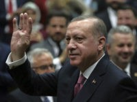Turkey's President Recep Tayyip Erdogan waves as he arrives to address members of his ruling party at the parliament in Ankara, Turkey, Tuesday, Feb. 20, 2018. Erdogan said Turkish troops involved in an offensive to drive out Syrian Kurdish militiamen from a Syrian enclave will soon begin a siege of the city of Afrin. (AP Photo/Burhan Ozbilici)