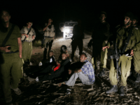 In this Aug. 20, 2007 file photo, a Sudanese refugee family sit on the ground surrounded by Israeli army soldiers after they crossed illegally from Egypt into Israel. The Israeli Cabinet voted unanimously Sunday, Dec. 11, 2011, to finance a $160 million program designed to staunch the flow of illegal African migrants into Israel by stepping up construction of a border fence and expanding a detention center to hold thousands of the new arrivals. (AP Photo/Ariel Schalit, File)