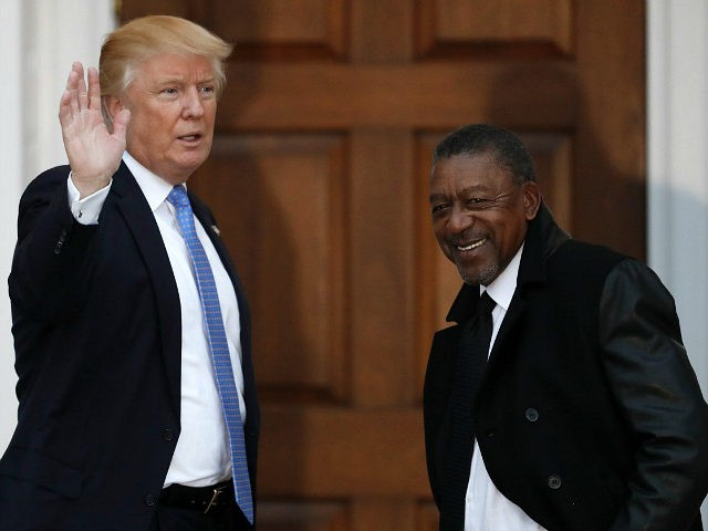 FILE - In this Nov. 20, 2016 file photo, President-elect Donald Trump stands with BET founder Robert Johnson at the Trump National Golf Club Bedminster clubhouse in Bedminster, N.J.. Johnson is one of dozens of people who have paraded into Trump's properties in New York and New Jersey in recent weeks for job interviews and other consultations with the Republican. Several described the meetings as serious, yet conversational, with the president-elect leading the discussion and asking questions extemporaneously, without consulting notes. (AP Photo/Carolyn Kaster, File)
