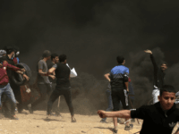 Palestinian protestors try to take down a section of barbed wire at the border fence with Israel, east of Gaza City in the central Gaza Strip, on April 13, 2018. Clashes erupted as thousands protested for a third consecutive Friday along Gaza's border with Israel after violence in which Israeli forces have killed 33 Palestinians and wounded hundreds of others. / AFP PHOTO / MAHMUD HAMS (Photo credit should read MAHMUD HAMS/AFP/Getty Images)