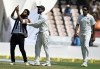A fan invades the pitch to take a selfie and hug Indian cricket captain Virat Kohli (C) during the first day's play of the second Test against the West Indies