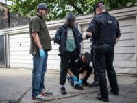 LONDON, ENGLAND - JULY 12: (EDITORS NOTE: Part of this image has been pixellated to obscure identity) A suspect is detained and searched by police officers after being arrested for alleged possession of a dangerous weapon near Elephant and Castle Station during Operation Sceptre on July 12, 2017 in London, …