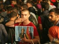 MUNICH, GERMANY - SEPTEMBER 05: A migrant from Syria holds a picture of German Chancellor Angela Merkel as he and approximately 800 others arrive from Hungary at Munich Hauptbahnhof main railway station on September 5, 2015 in Munich, Germany. Thousands of migrants are traveling to Germany following an arduous ordeal …