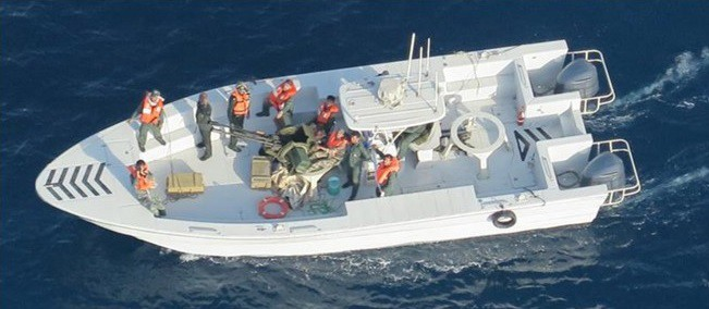 This image released by the U.S. Department of Defense on Monday, June 17, 2019, and taken from a U.S. Navy helicopter, shows what the Navy says is the Islamic Revolutionary Guard Corps Navy after removing an unexploded limpet mine from the M/T Kokuka Courageous. (U.S. Department of Defense via AP)