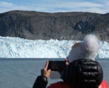 EQIP SERMIA, GREENLAND - JULY 31: A visitor on a tourist boat photographs the 200 meter tall face of the Eqip Sermia glacier, also called the Eqi glacier, during unseasonably warm weather on July 31, 2019 at Eqip Sermia, Greenland. The Eqip Sermia glacier is located approximately 350km north of …