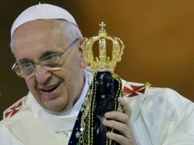 "Pope Francis holds an iimage of Our Lady of Aparecida during the Holy Mass at the National Shrine of Our Lady of Aparecida, in Aparecida, state of Sao Paulo, on July 24, 2013. Pope Francis warned Catholics on Wednesday against ""ephemeral idols"" like money at his first public mass in …"