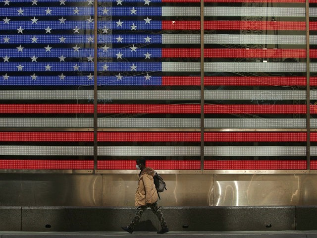 NEW YORK, NEW YORK - APRIL 25: A pedestrian, wearing a protective face mask walks past the American flag video board in Times Square during the coronavirus pandemic on April 25, 2020 in New York City. COVID-19 has spread to most countries around the world, claiming over 200,000 lives with …