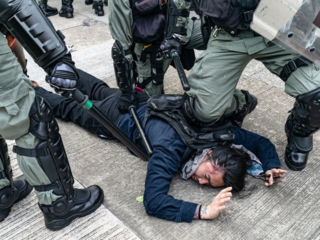 """HONG KONG - AUGUST 24: A protester is detained by riot police during an anti-government rally in Kowloon Bay district on August 24, 2019 in Hong Kong, China. Pro-democracy protesters have continued rallies on the streets of Hong Kong against a controversial extradition bill since 9 June as the city plunged into crisis after waves of demonstrations and several violent clashes. Hong Kong's Chief Executive Carrie Lam apologized for introducing the bill and declared it """"dead"""", however protesters have continued to draw large crowds with demands for Lam's resignation and completely withdraw the bill. (Photo by Anthony Kwan/Getty Images)"""