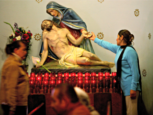 SAN DIEGO - APRIL 16: A church congregant touches a statue of Jesus and Mary during Easter Mass at Our Lady of Guadeloupe Catholic Church April 16, 2006 in the Barrio Logan section of San Diego, California. (Photo by Sandy Huffaker/Getty Images)