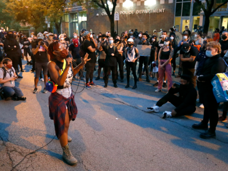 Ariel Atkins, a lead organizer for Black Lives Matter Chicago, leads a protest Monday, Aug. 10, 2020, outside the Chicago Police Department's District 1 station in Chicago. (AP Photo/Charles Rex Arbogast)