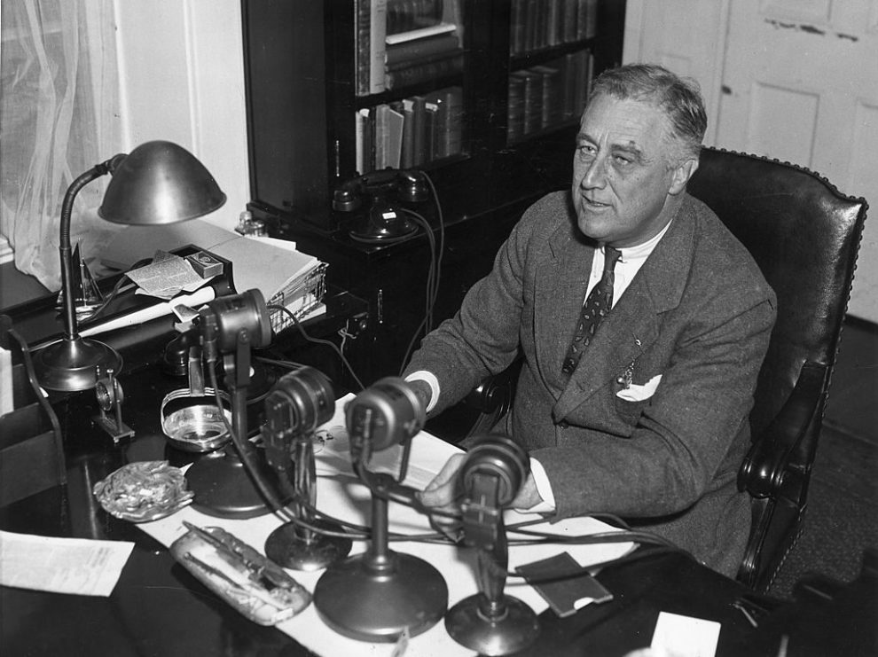 circa 1935: US president Franklin Delano Roosevelt (1882-1945) speaks into four radio microphones, which sit on his desk during one of his live nationwide 'fireside chat' broadcasts. (Photo by Hulton Archive/Getty Images)