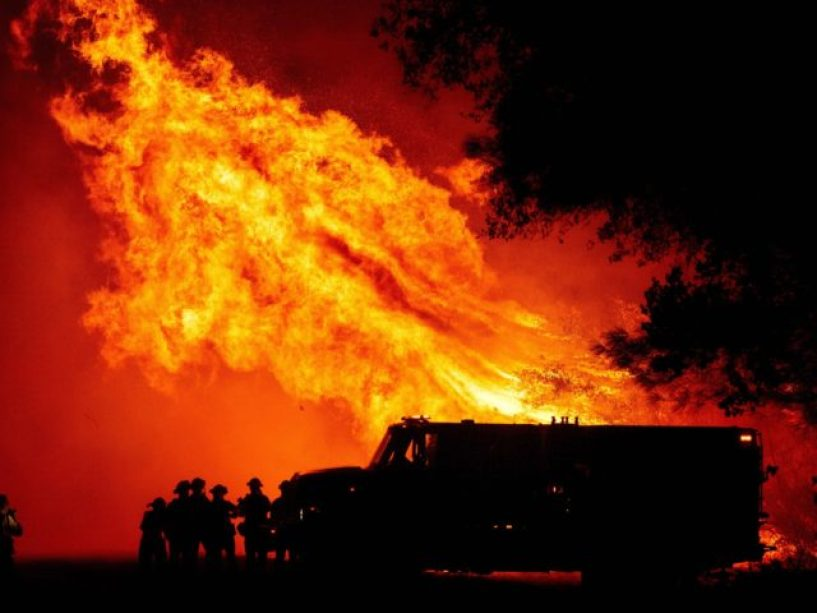 TOPSHOT - Butte county firefighters watch as flames tower over their truck during the Bear fire in Oroville, California on September 9, 2020. - Dangerous dry winds whipped up California's record-breaking wildfires and ignited new blazes, as hundreds were evacuated by helicopter and tens of thousands were plunged into darkness …