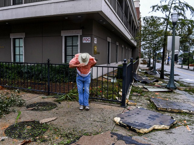 """TOPSHOT - A man saves his hat in the strong wind during Hurricane Sally landfall in Mobile, Alabama on September 16, 2020. - Hurricane Sally barrelled into the US Gulf Coast early Wednesday, with forecasts of drenching rains that could provoke """"historic"""" and potentially deadly flash floods.The National Hurricane Center (NHC) said the Category 2 storm hit Gulf Shores, Alabama at about 4:45 am (0945 GMT), bringing maximum sustained winds of about 105 miles (165 kilometers) per hour.""""Historic life-threatening flooding likely along portions of the northern Gulf coast,"""" the Miami-based center had warned late Tuesday, adding the hurricane could dump up to 20 inches (50 centimeters) of rain in some areas. (Photo by CHANDAN KHANNA / AFP) (Photo by CHANDAN KHANNA/AFP via Getty Images)"""