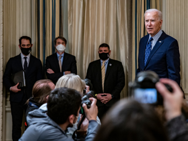 President Joe Biden stops to answer questions from reporters after speaking in the State Dining Room with Vice President Kamala Harris behind him following the passage of the American Rescue Plan in the U.S. Senate at the White House on March 6, 2021 in Washington, DC. The Senate passed the latest COVID-19 relief bill by 50 to 49 on a party-line vote, after an all-night session. (Photo by Samuel Corum/Getty Images)